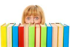 Muchacha sorprendida con los libros del color de la pila. Aislado Imagen de archivo