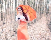 Muchacha sorprendida con un paraguas en una mano Imagen de archivo