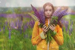 Muchacha sorprendida con un ramo de Lupines en un campo en la lluvia Fotos de archivo