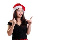 Muchacha sorprendida de la Navidad que señala en el copyspace Imagen de archivo libre de regalías