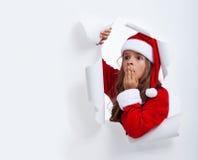 Muchacha sorprendida de Papá Noel que mira a través del agujero en papel Fotos de archivo libres de regalías