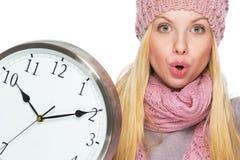 Muchacha sorprendida del adolescente en sombrero y bufanda del invierno con el reloj Foto de archivo
