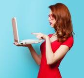 Muchacha sorprendida del pelirrojo con el ordenador portátil imagen de archivo
