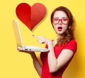 Muchacha sorprendida del pelirrojo con el ordenador portátil y el corazón imágenes de archivo libres de regalías