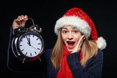 Muchacha sorprendida en el sombrero de Papá Noel con el despertador Fotografía de archivo