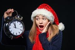 Muchacha sorprendida en el sombrero de Papá Noel con el despertador Imagen de archivo libre de regalías