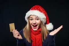 Muchacha sorprendida en el sombrero de Papá Noel con la tarjeta del crédito en blanco Imagen de archivo libre de regalías