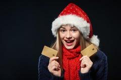 Muchacha sorprendida en el sombrero de Papá Noel con la tarjeta del crédito en blanco Imagenes de archivo