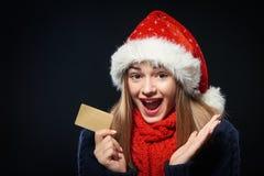 Muchacha sorprendida en el sombrero de Papá Noel con la tarjeta del crédito en blanco Foto de archivo