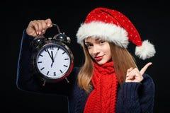 Muchacha sorprendida en el sombrero de Papá Noel con el reloj Fotografía de archivo