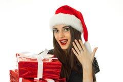 Muchacha sorprendida en el sombrero de santa con el regalo rojo Imágenes de archivo libres de regalías