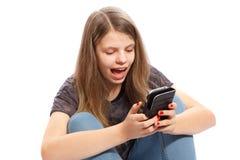 Muchacha sorprendida en el teléfono Imagen de archivo