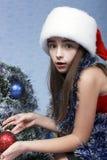 Muchacha sorprendida en un casquillo con la Navidad Imagen de archivo