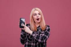 Muchacha sorprendida, escuchando un smartphone quebrado con un estetoscopio En un fondo rosado imágenes de archivo libres de regalías