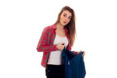 Muchacha sorprendida jóvenes del estudiante con la presentación de la mochila aislada en el fondo blanco en estudio Imagen de archivo libre de regalías