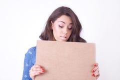 Muchacha sorprendida linda con una muestra en manos Fotografía de archivo libre de regalías