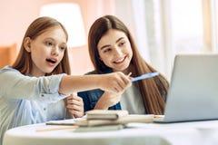 Muchacha sorprendida que atrae la atención de las hermanas a la pantalla del ordenador portátil Fotos de archivo
