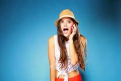 Muchacha sorprendida que habla en el teléfono móvil Fotografía de archivo