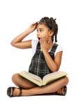 Muchacha sorprendida que lee un libro Foto de archivo libre de regalías