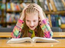 Muchacha sorprendida que lee un libro en la biblioteca Imágenes de archivo libres de regalías