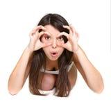 Muchacha sorprendida que mira con binocular imaginario Fotos de archivo