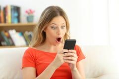 Muchacha sorprendida que mira el contenido elegante del teléfono Fotografía de archivo libre de regalías