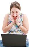 Muchacha sorprendida que mira en computadora portátil Fotografía de archivo libre de regalías