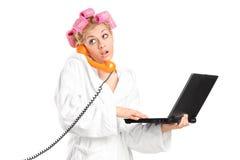 Muchacha sorprendida que sostiene el ordenador portátil y que habla en el teléfono Imágenes de archivo libres de regalías