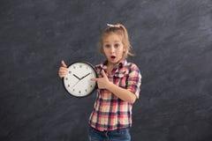 Muchacha sorprendida que sostiene el reloj grande, señalando en él Foto de archivo