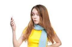 Muchacha sorprendida que sostiene el teléfono en su mano. Fotografía de archivo libre de regalías