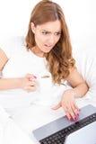 Muchacha sorprendida que usa el ordenador portátil en casa con el facial expreso Fotos de archivo