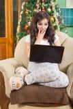 Muchacha sorprendida que usa el ordenador portátil que se sienta en el sofá ind relajado Imagen de archivo libre de regalías