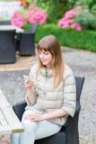 Muchacha studient joven hermosa feliz con el teléfono elegante blanco al aire libre el día de fiesta que manda un SMS y que sonrí Imagenes de archivo