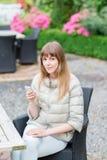 Muchacha studient joven hermosa feliz con el teléfono elegante blanco al aire libre el día de fiesta que manda un SMS y que sonrí Fotografía de archivo