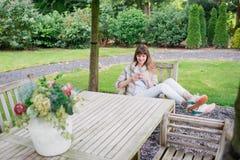 Muchacha studient joven hermosa feliz con el teléfono elegante blanco al aire libre el día de fiesta que manda un SMS y que sonrí Fotos de archivo libres de regalías
