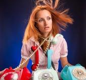 Muchacha subrayada con los teléfonos Imagen de archivo libre de regalías