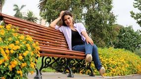 Muchacha subrayada que se sienta en parque Imagen de archivo libre de regalías