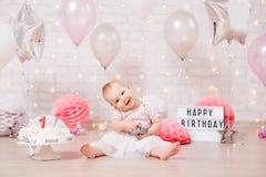 Muchacha sucia divertida y torta de cumpleaños rota sobre la pared de ladrillo con las luces y los globos fotografía de archivo