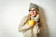 Muchacha tímida agradable del inconformista en ropa del invierno con una taza Imagen de archivo