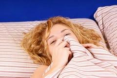 Muchacha tímida, joven, rubia que mira a escondidas sobre ropa de cama Imagenes de archivo