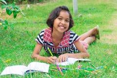 Muchacha tailandesa asiática que miente en la hierba con el lápiz y el homew coloreados Fotografía de archivo libre de regalías