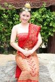 Muchacha tailandesa joven en el equipo tradicional que se sienta y que presenta en el templo de Chalong Imagen de archivo