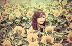 Muchacha tailandesa linda en el medio del campo hermoso del girasol en vin Fotos de archivo