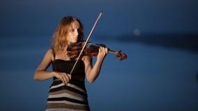 Muchacha talentosa que toca el violín que se coloca en a almacen de metraje de vídeo