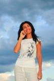 Muchacha, teléfono y cielo Foto de archivo