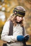 Muchacha texting con el teléfono celular en un parque del otoño Fotografía de archivo