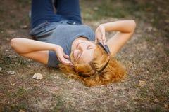 Muchacha tranquila del jengibre en los auriculares que se relajan en un fondo de la hierba Concepto del tiempo libre Fotos de archivo