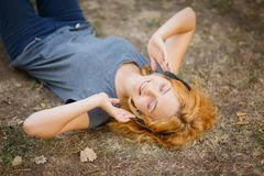 Muchacha tranquila del jengibre en los auriculares que se relajan en un fondo de la hierba Concepto del tiempo libre Imagen de archivo libre de regalías