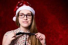 Muchacha trastornada con los vidrios en un sombrero de santa en un fondo rojo Foto de archivo libre de regalías