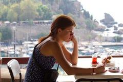 Muchacha trastornada de la tristeza que se sienta en café y que hojea a través de un teléfono elegante Antalya, ciudad vieja de l Foto de archivo libre de regalías
